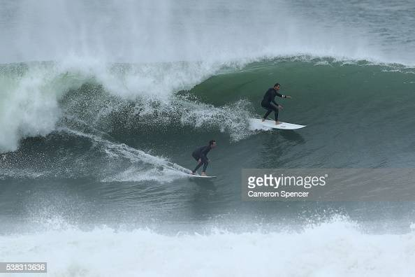 Surfers ride a wave at North Narrabeen as large swell hits the Australian East Coast on June 6 2016 in Sydney Australia Torrential rain over the...