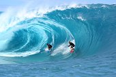 Surfers ride a wave during the shooting of a remake of the 1991 classic 'Point Break' on September 11 2014 in the Hava'e pass in Teahupoo on the...