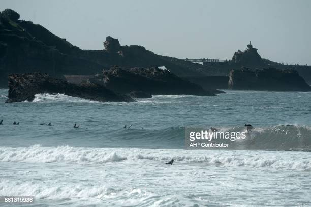 Surfers ride a wave in La Grande Plage of Biarritz western France on October 14 2017 GAIZKA