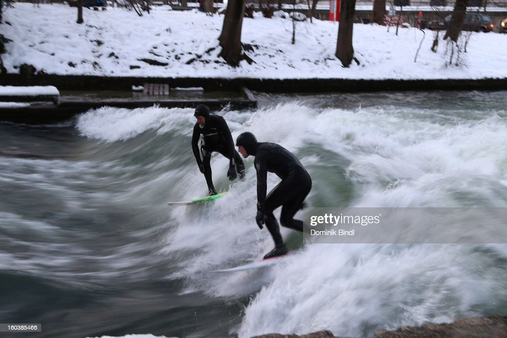 Surfers ride the Eisbach wave on January 23, 2013 in Munich, Germany.