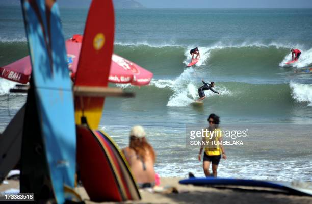 Surfers ride waves at Kuta beach on Bali island on July 13 2013 The Indonesian government has set the ambitious target of welcoming a total of nine...
