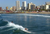 Surfers ride waves at South Beach in Durban on June 20 2010 during the South Africa 2010 World Cup footall tournament AFP PHOTO / JAVIER SORIANO