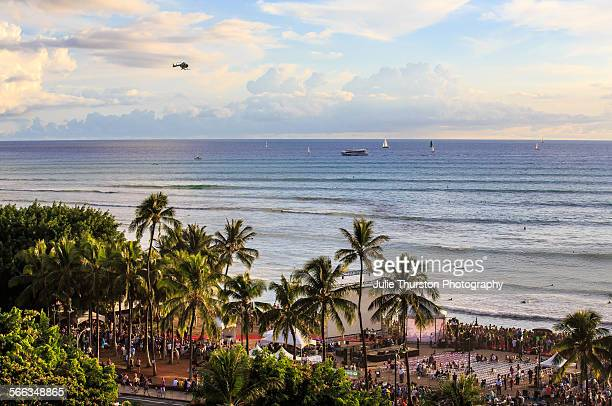 Surfers ride waves helicopters fly above as people gather on the beach for the celebrity filled event Sunset on the Beach Season 5 Premier of the TV...