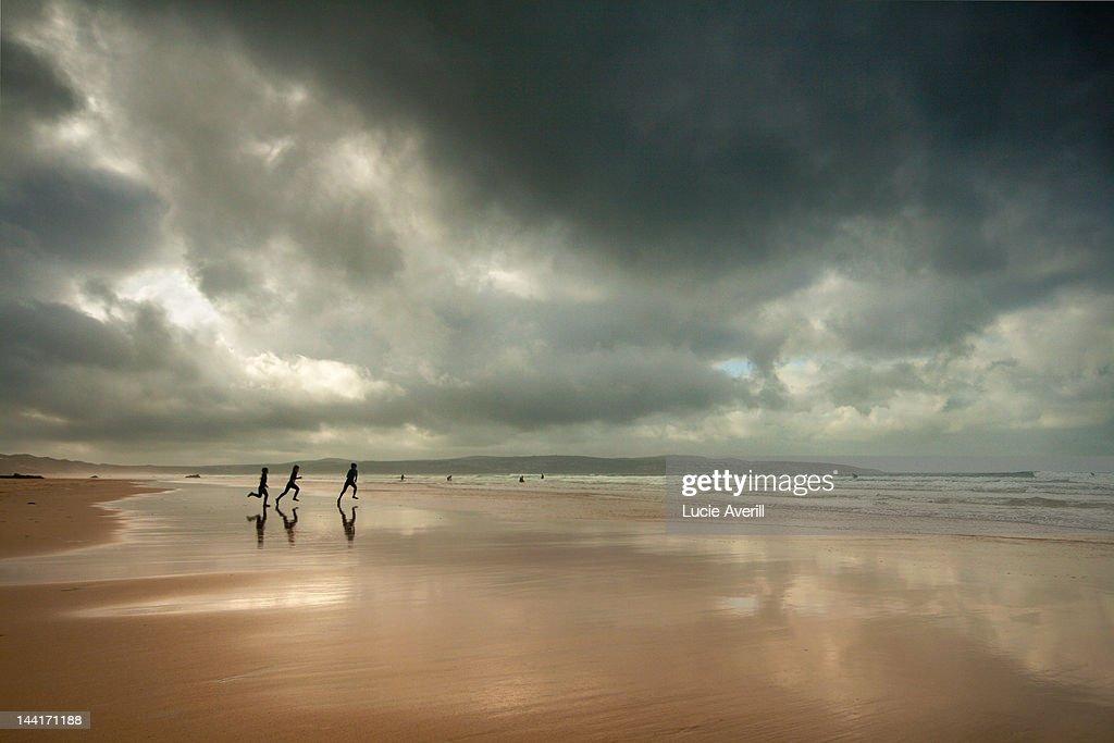Surfers running on beach