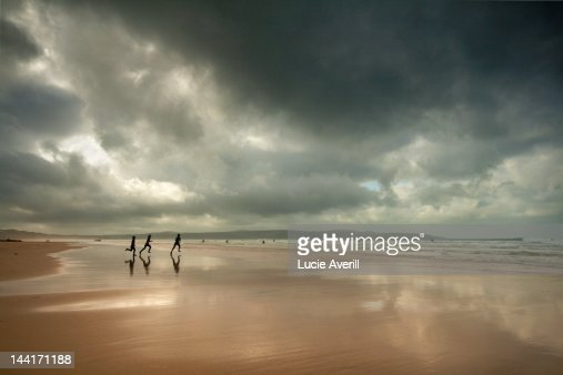 Surfers running on beach : Stock Photo