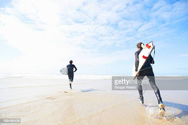 Surfers running towards the sea.