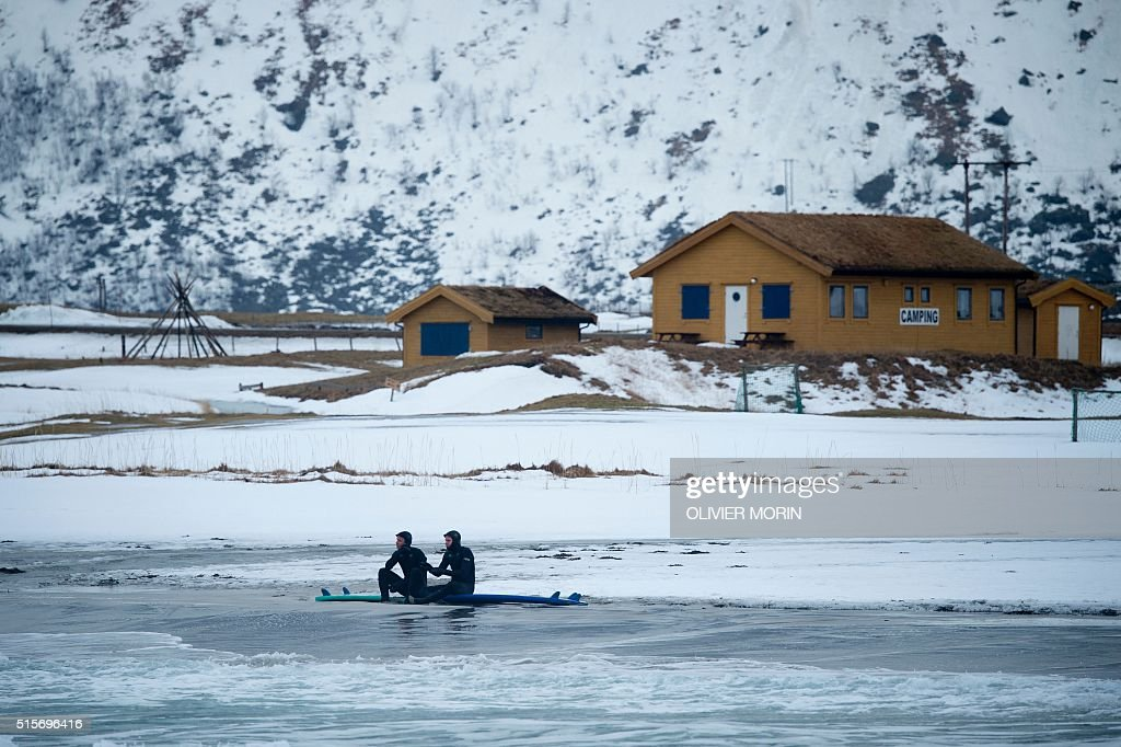 Surfers sit on their board as they have a break during a surf session at the snow covered beach of Flackstad, on Lofoten Island, Arctic Circle, on March 12, 2016. Surfers from all over the world come to Lofoten island to surf in extrem conditions. Ocean temperature is 5-6 °C, air temperature around 0°C in spite of a weather very unstable. / AFP / OLIVIER