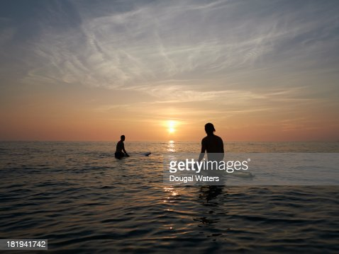 Surfers sitting on boards at sunset. : Stock Photo
