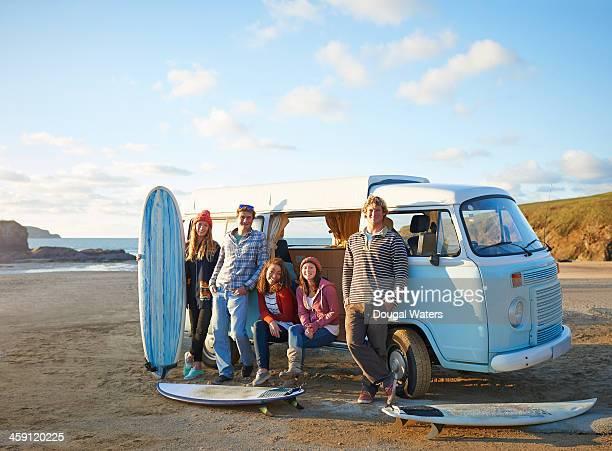 Surfers stand beside camper van on beach.