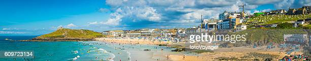Surfers sunbathers seaside ocean resort beach panorama St Ives Cornwall