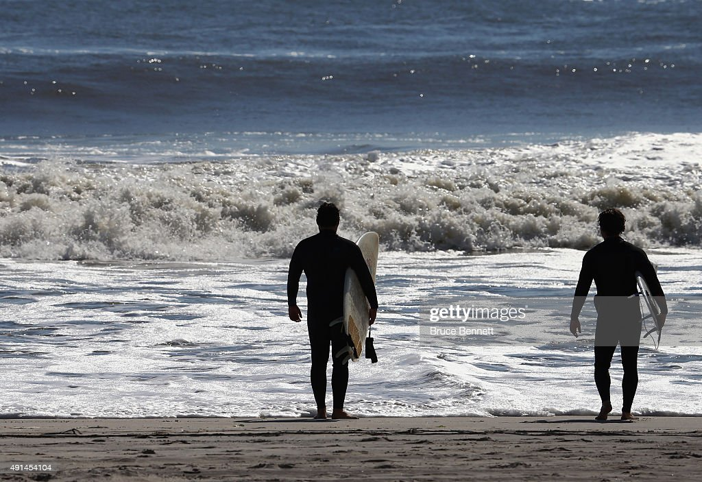 Surfers survey the five to seven foot swells coming off the Atlantic Ocean on October 5 2015 in Long Beach New York The higher than average wave...