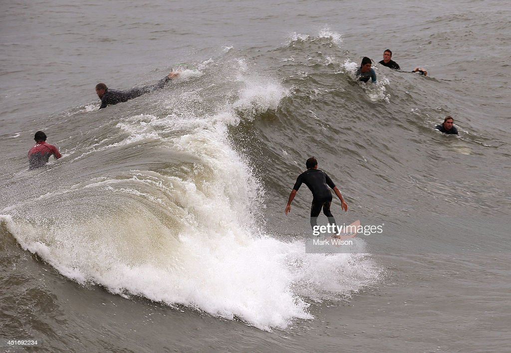 Surfers take advantage of the large waves left by Hurricane Arthur, July 4, 2014 in Avalon, North Carolina. Hurricane Arthur hit North Carolina's outer banks overnight causing widespread power outages, flooding and damage and has since weakened to a Category 1 as of Friday morning.