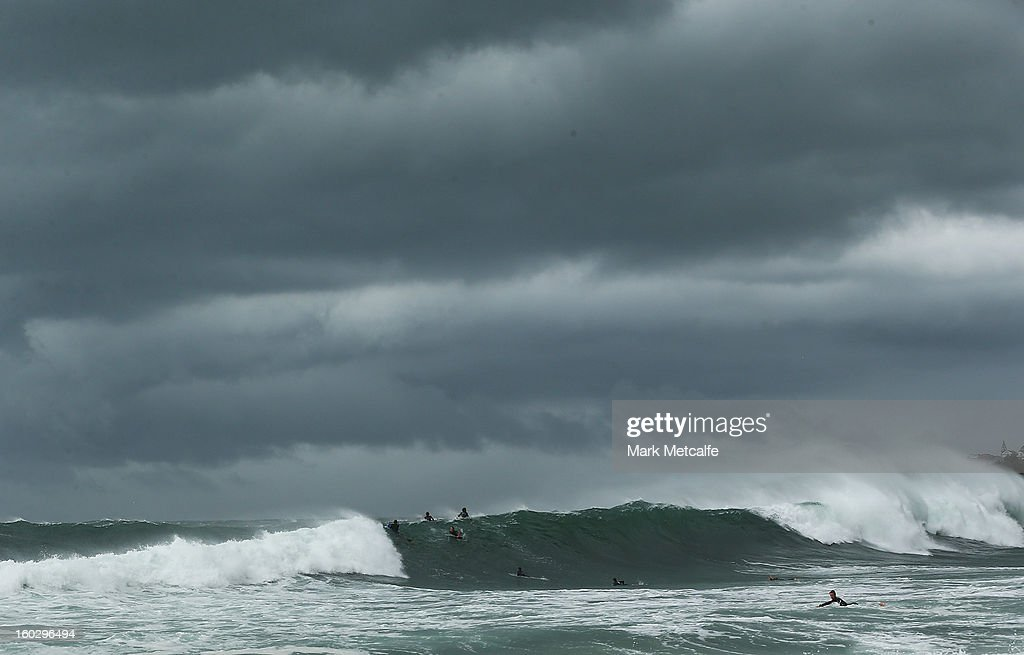 Surfers take on the large swells as storm clouds gather at Coogee Beach after winds and rain battered Sydney last night on January 29, 2013 in Sydney, Australia. Parts of Sydney are experienced record rainfall after ex-cyclone Oswald swept through the city last night.