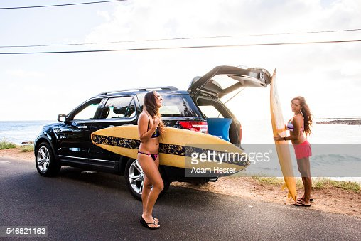 Surfers unloading surfboards from car near beach