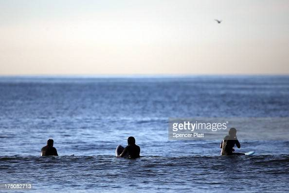 Surfers wait for waves during an early morning surfing session at Rockaway Beach on July 31 2013 in the Queens borough of New York City Despite the...