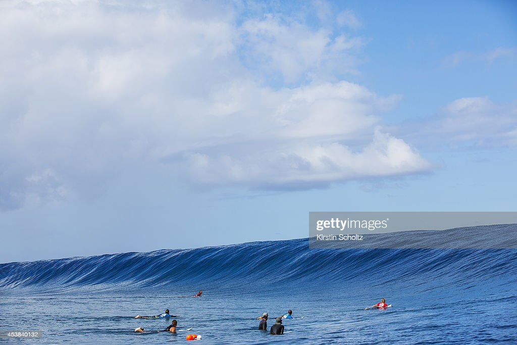 Surfers wait in the lineup as a swell rises at the Billabong Pro Tahiti on August 19, 2014 in Teahupo'o, French Polynesia.