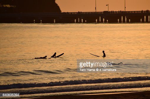 Surfers waiting for wave in the sunset beach : ストックフォト
