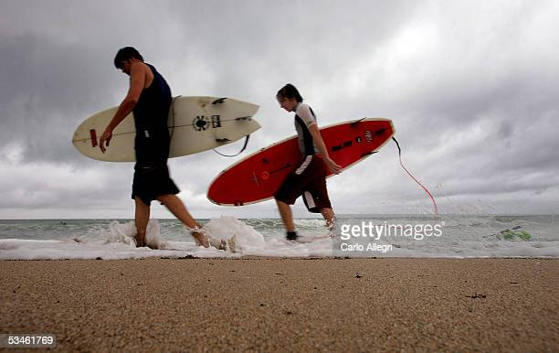 Surfers walk along the beach in advance of Tropical Storm Katrina August 25 2005 in Ft Lauderdale Florida Katrina is expected to make landfall later...