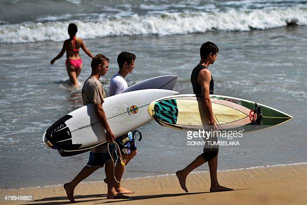 Surfers walk at the beach in Kuta on Bali island on June 29 2015 Surfers are anticipating bigger waves than usual in the coming days off the island...