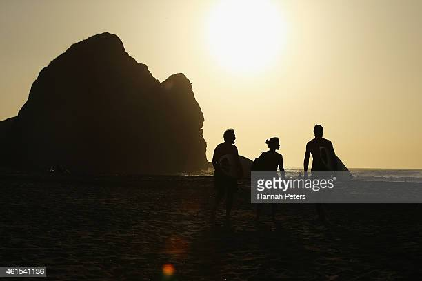 Surfers walk out for a practice session ahead of the New Zealand Surf Nationals at Piha Beach on January 09 2015 in Auckland New Zealand