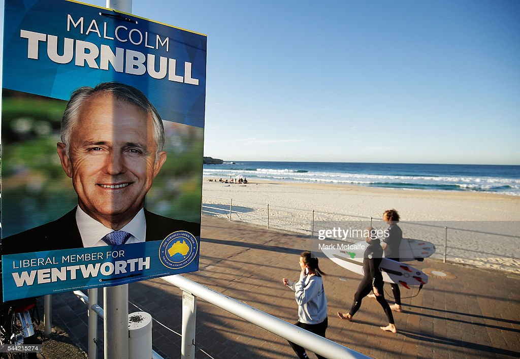 Surfers walk past an election poster at Bondi Beach in the electorate of Wentworth on July 2, 2016 in Sydney, Australia. Voters head to the polls today to elect the 45th parliament of Australia.
