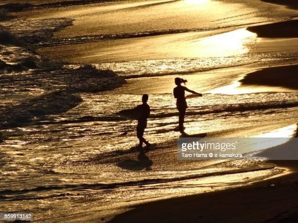 Surfers walking on the sunset beach in Kamakura city in Kanagawa prefecture in Japan