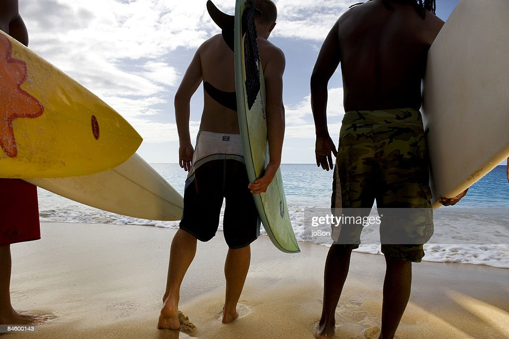 Surfers walking to water on beach with surfboards : Stock Photo