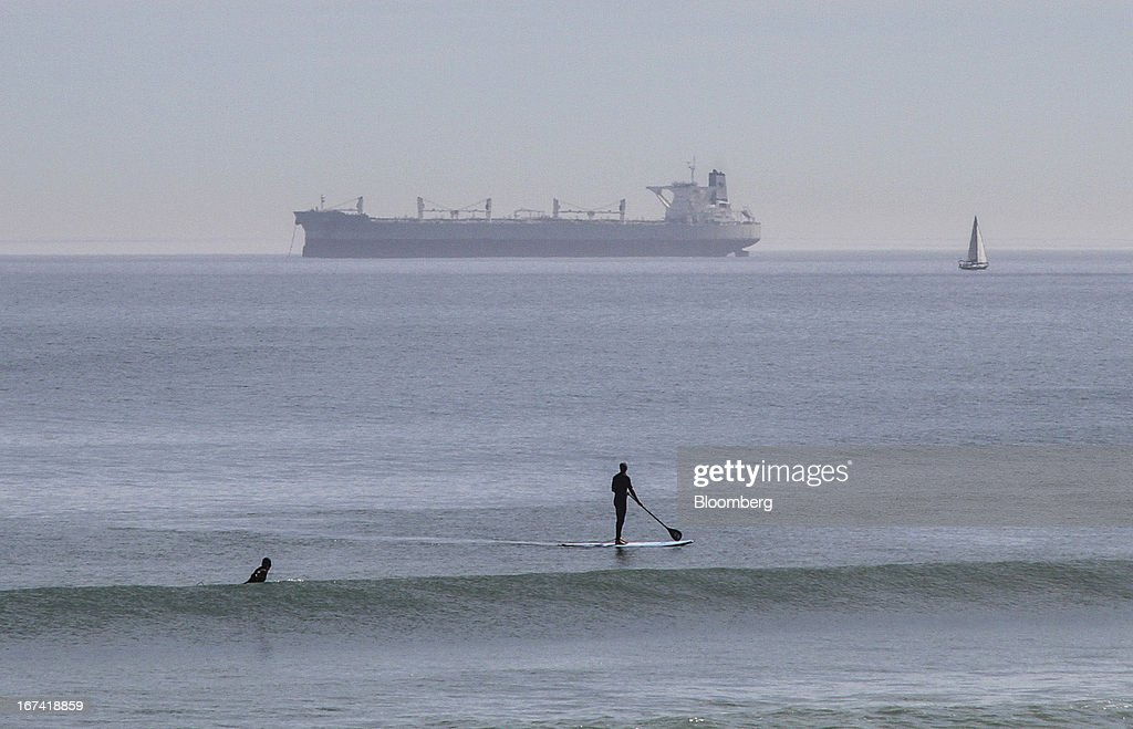 Surfers watch as a cargo ship approaches the entrance to the port in Cape Town, South Africa, on Wednesday, April 24, 2013. South Africa's gross domestic product is forecast to expand 2.6 percent this year, compared with 2.5 percent in 2012, according to the country's central bank. Photographer: Nadine Hutton/Bloomberg via Getty Images