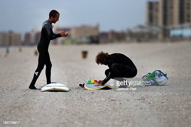 Surfers wax their boards at Rockaway beach on October 9 2013 in the Queens borough of New York City Nearly one year after Hurricane Sandy devastated...