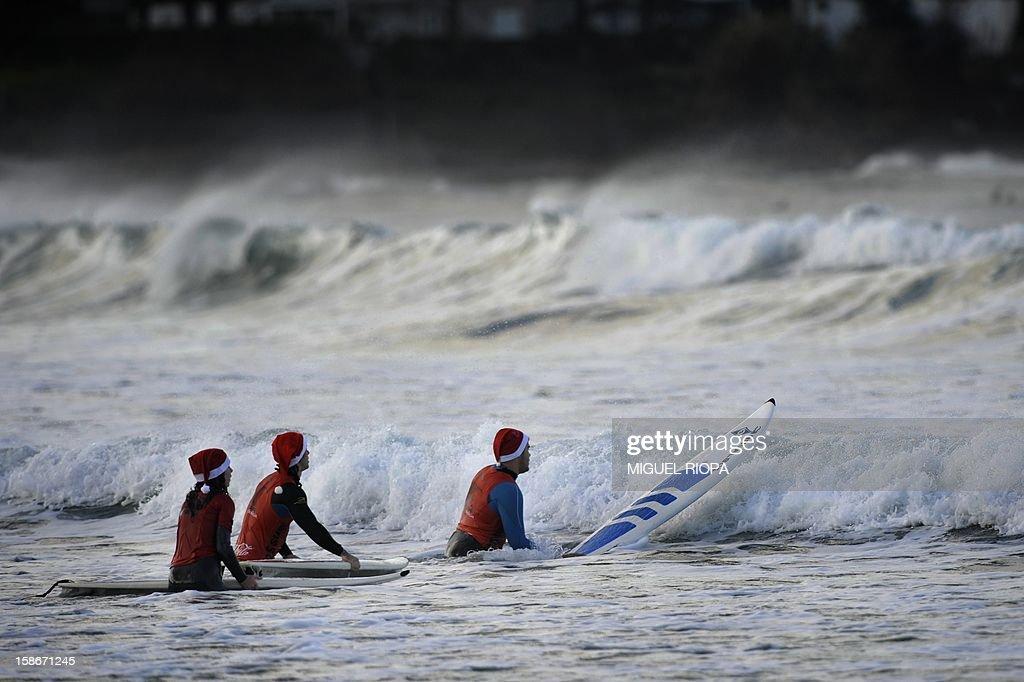 Surfers wearing a Santa Claus hat surf at Patos Beach, near Vigo, northwestern Spain, on December 23, 2012.