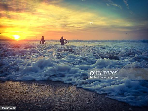 Surfers With Surfboard Walking On Beach Against Sky During Sunset