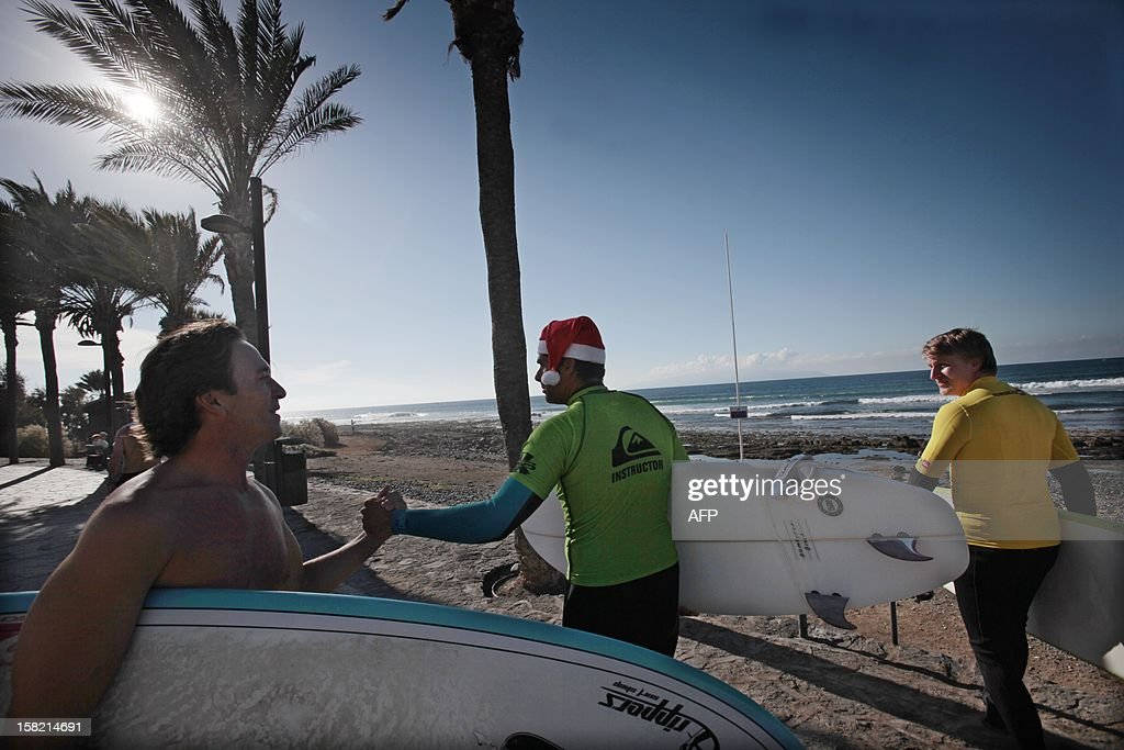 A surfeur wearing a Santa hat shakes hands with another surfeur at the beach of Las Americas on the Spanish Canary Island of Tenerife on December 11, 2012.