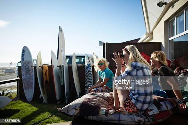 Surfgirl looking at sea with binoculars