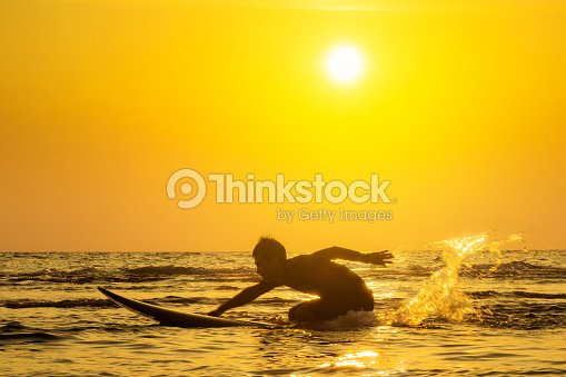 Surfing at Sunset. Outdoor Active Lifestyle. Summer water sport.