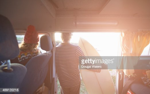 Surfing couple look out to sea from camper van.