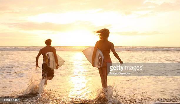 Surfing couple run through shallows towards surf