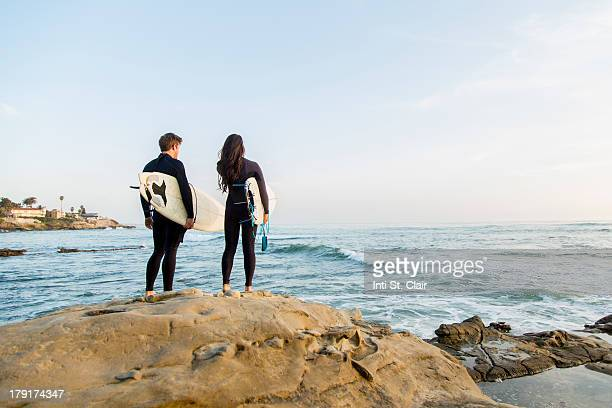 Surfing couple standing on cliff looking at waves