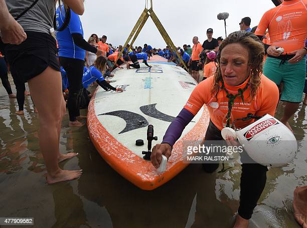 Surfing legend Kim Hamrock known as 'Danger Woman' waxes a board as sixty six surfers from Huntington Beach prepare to break the 'Guinness Book of...