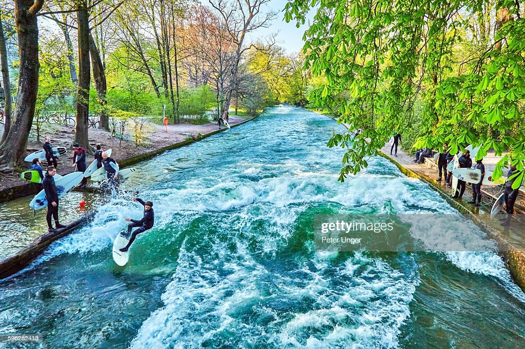 Surfers at Eisbach, small artificial river at the English Garden in the city of Munich.