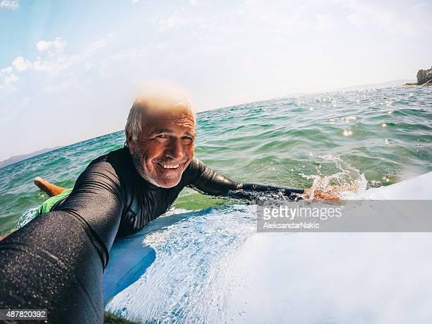 セルフィーサーフィンをする老人男性