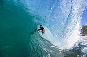 Surfer surfing hollow wave tube ride closeup up water action photo sequence.