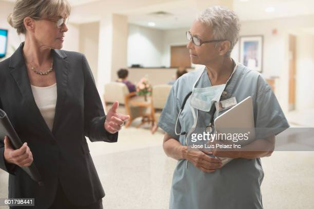 Surgeon and businesswoman talking in hospital