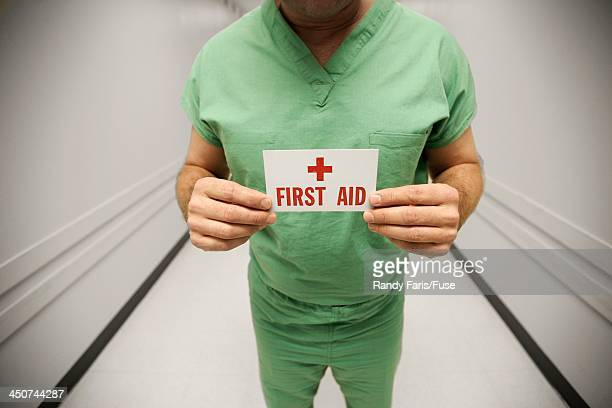 Surgeon Holding First Aid Card