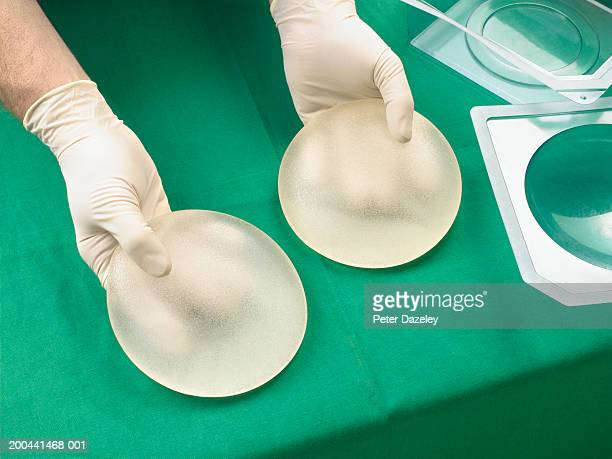 Surgeon holding silicone breast implants, close-up, elevated view