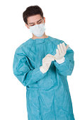 Young male surgeon in a mask and gown putting on disposable surgical gloves before going in to theatre isolated on white