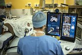 A surgeon sitting in front of screens of a Focal Onedevice performs a robotassisted prostate tumorectomy using ultrasound imaging on April 10 2014 at...