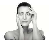 Anti aging treatment and plastic surgery concept. Beautiful young woman with hands on cheeks and eyes closed with a serene expression in a beauty, skincare and spa concepts. Perfect skin. Monochrome p