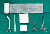 surgery tools ,scissors ,roll gauze,bandage,pad,cramp,blade,knife on green surgical dress background ,bird eye view