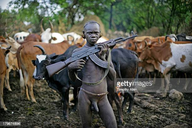 Suri tribal boy with gun protects cattle