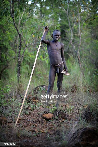 Suri tribal boy with stick and money